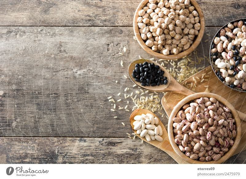 Uncooked assorted legumes in wooden bowl on wood Food Grain Nutrition Eating Organic produce Vegetarian diet Diet Bowl Spoon Natural Brown White Legume Beans