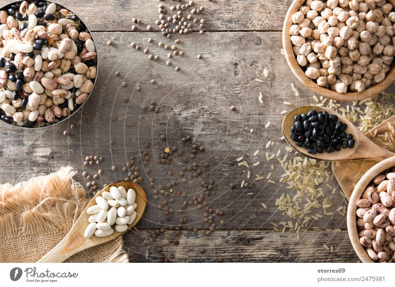 Uncooked assorted legumes in wooden bowl Food Grain Nutrition Organic produce Vegetarian diet Diet Bowl Spoon Natural Brown Black White Legume Beans Chickpeas