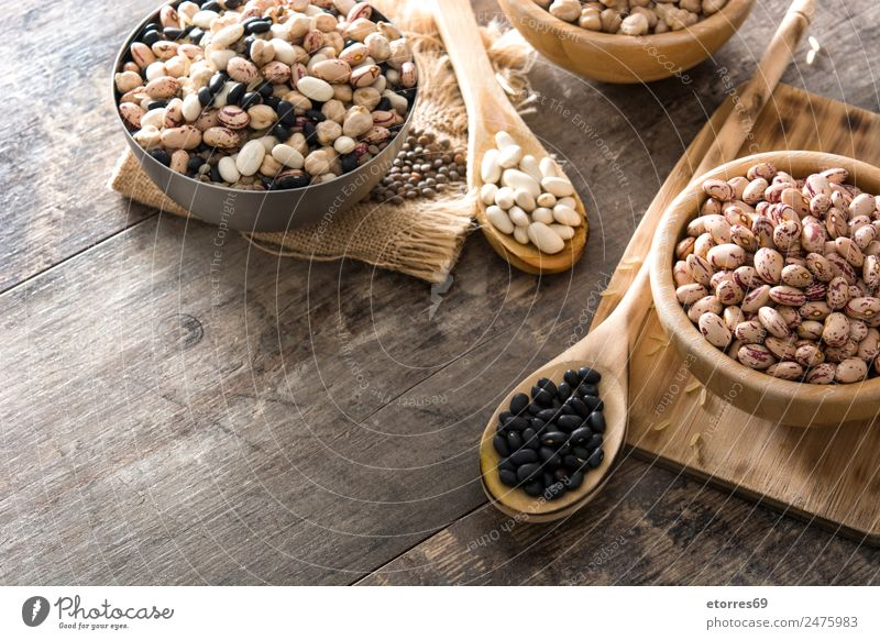 Uncooked assorted legumes in wooden bowl on wood Food Grain Nutrition Eating Organic produce Vegetarian diet Diet Bowl Spoon Nature Brown White Legume Mix Beans