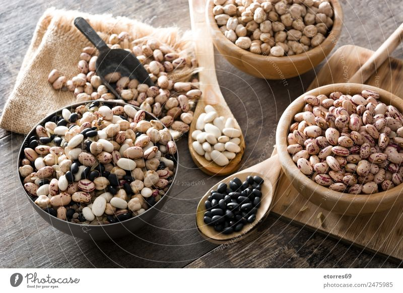 Uncooked assorted legumes in wooden bowl Food Grain Nutrition Organic produce Vegetarian diet Diet Bowl Spoon Natural Brown Black White Legume Beans