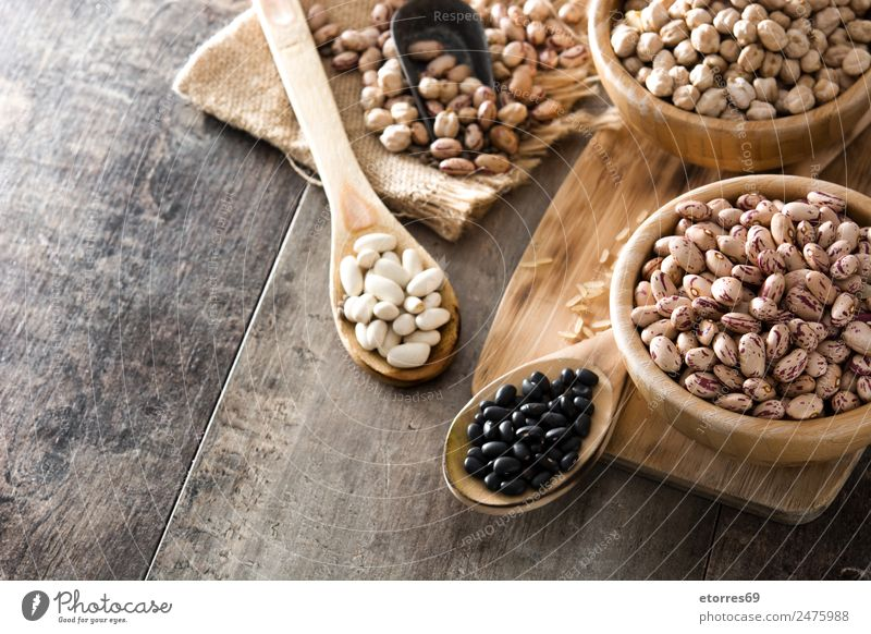 Uncooked assorted legumes in wooden bowl Food Grain Nutrition Organic produce Vegetarian diet Diet Bowl Spoon Natural Brown Legume Beans Chickpeas