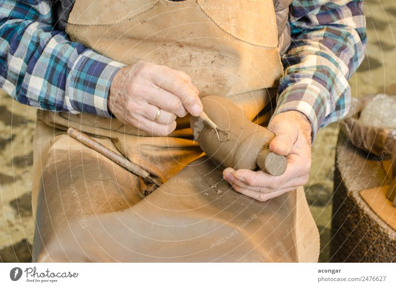 Old hands of a potter shaping a clay figure Handicraft Work and employment Profession Craftsperson Tool 60 years and older Senior citizen Art Artist Brown
