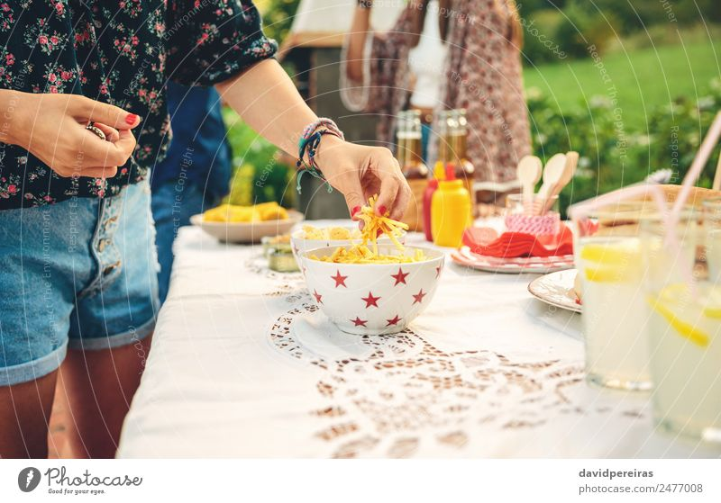 Woman hand taking chips potatoes from bowl Nature Man Summer Hand Joy Adults Lifestyle Garden Group Friendship Leisure and hobbies Authentic To enjoy Table