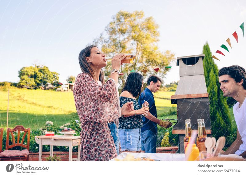 Woman drinking beer in a barbecue with friends Meat Lunch Drinking Alcoholic drinks Beer Bottle Lifestyle Joy Happy Leisure and hobbies Summer Garden Table