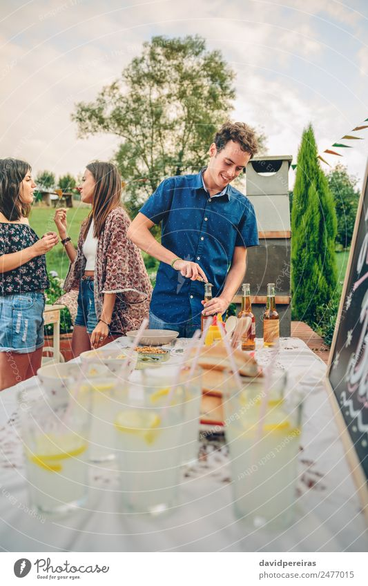 Man opening beer bottle in summer barbecue Eating Lunch Lemonade Alcoholic drinks Beer Bottle Straw Lifestyle Joy Happy Leisure and hobbies Summer Garden Table