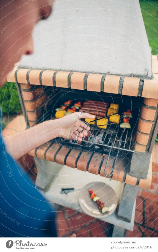 Unrecognizable young man cooking meal in barbecue Sausage Vegetable Lifestyle Joy Happy Relaxation Summer Garden Human being Man Adults Friendship Hand Nature