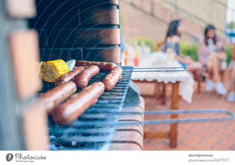 Sausages and corn cobs cooked in a barbecue Vegetable Lunch Lifestyle Joy Happy Relaxation Leisure and hobbies Summer Garden Table To talk Woman Adults