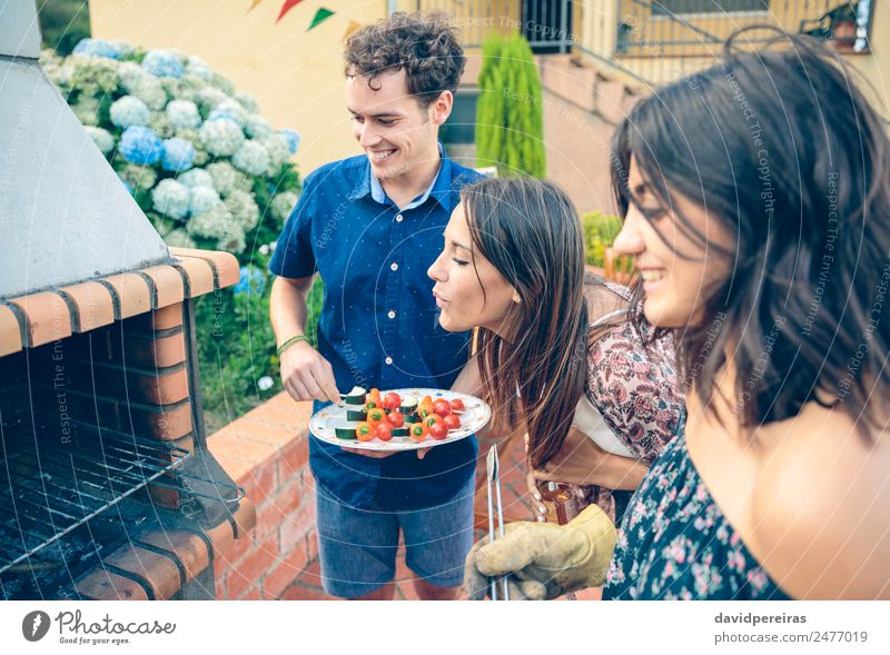 Group of friends cooking in a summer barbecue Vegetable Lunch Alcoholic drinks Beer Plate Bottle Lifestyle Joy Happy Leisure and hobbies Summer Garden To talk
