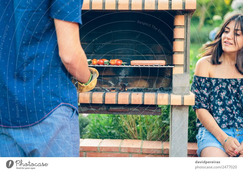 Man cooking sausages and vegetable skewers in a barbecue Sausage Vegetable Lifestyle Joy Happy Relaxation Summer Garden To talk Woman Adults Friendship Hand