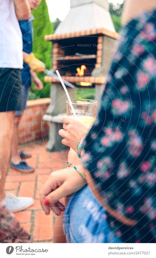 Woman holding lemonade glass and friends cooking in barbecue Sausage Lunch Lemonade Lifestyle Joy Happy Relaxation Leisure and hobbies Summer Garden To talk