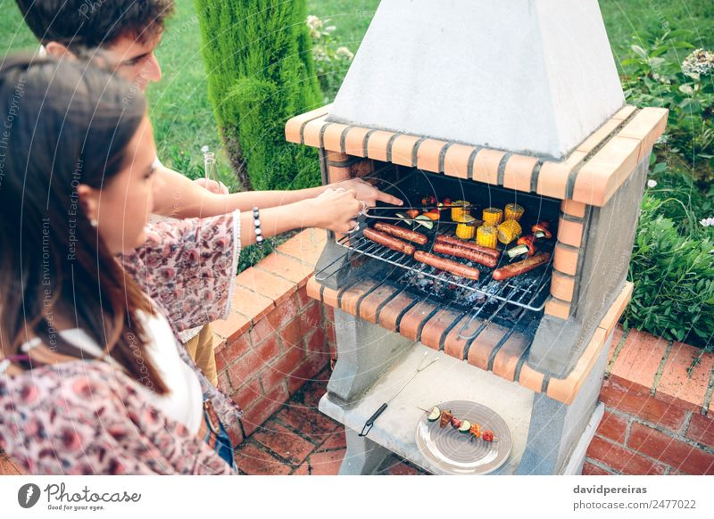 Friends cooking in barbecue on summer party Sausage Vegetable Lifestyle Joy Happy Relaxation Leisure and hobbies Summer Garden Woman Adults Man Friendship Hand