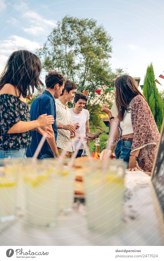 Group of friends having fun in a summer barbecue Meat Sausage Lunch Lemonade Alcoholic drinks Beer Straw Lifestyle Joy Happy Leisure and hobbies Summer Garden