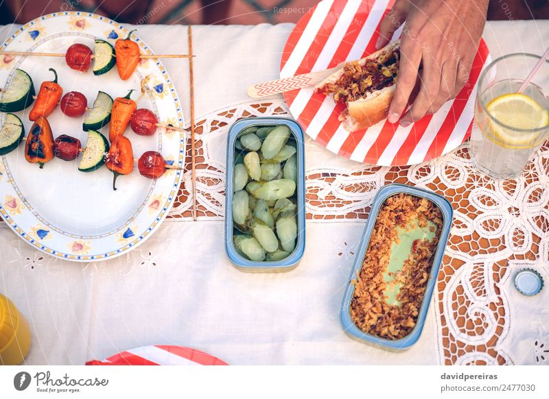Male hand holding hot dog on red striped plate Sausage Bread Roll Lunch Fast food Lemonade Plate Lifestyle Joy Happy Summer Human being Man Adults Friendship