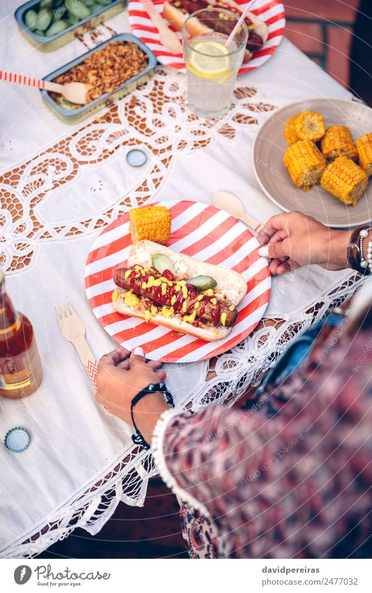 Woman holding plate with hot dog and corn Sausage Bread Roll Fast food Lemonade Alcoholic drinks Beer Plate Bottle Spoon Lifestyle Joy Happy Summer Table Adults