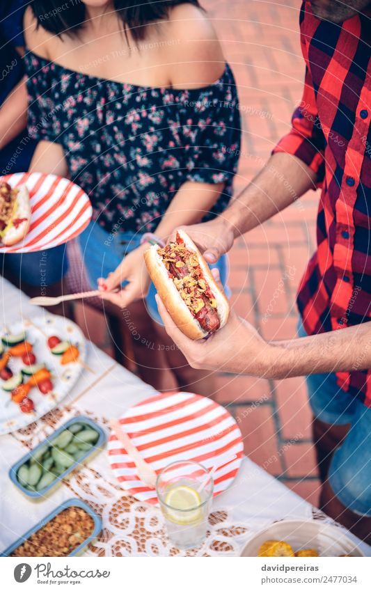 Man holding hot dog in barbecue with friends Sausage Bread Roll Eating Fast food Lemonade Plate Lifestyle Joy Happy Summer Table Woman Adults Friendship Hand