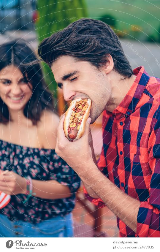 Young man eating hot dog and woman laughing in background Sausage Bread Roll Lunch Fast food Lifestyle Joy Happy Summer Woman Adults Man Friendship Hand Group