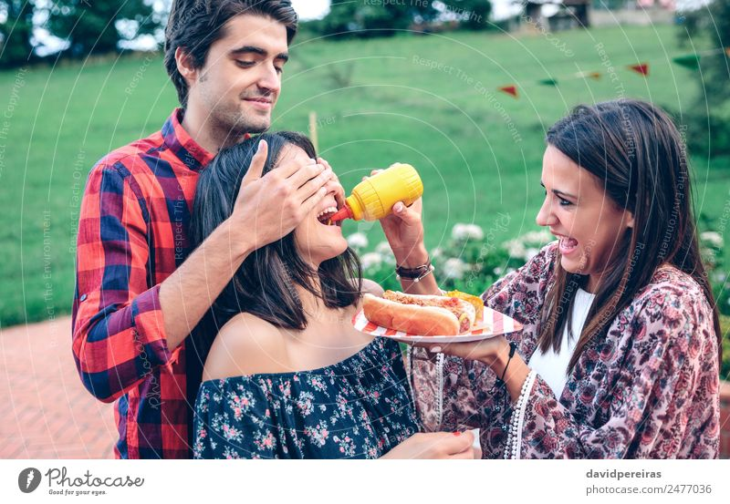 Man holding hot dog in barbecue with friends Sausage Eating Fast food Plate Lifestyle Joy Happy Summer Woman Adults Friendship Mouth Hand To enjoy Smiling