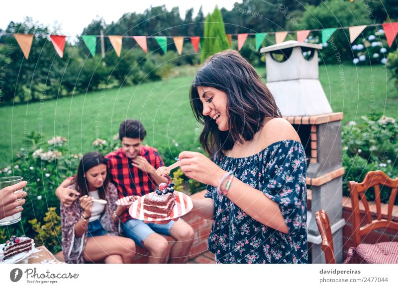 Woman eating piece of cake in summer party Eating Plate Spoon Lifestyle Joy Happy Leisure and hobbies Summer Garden To talk Adults Man Friendship Group Nature