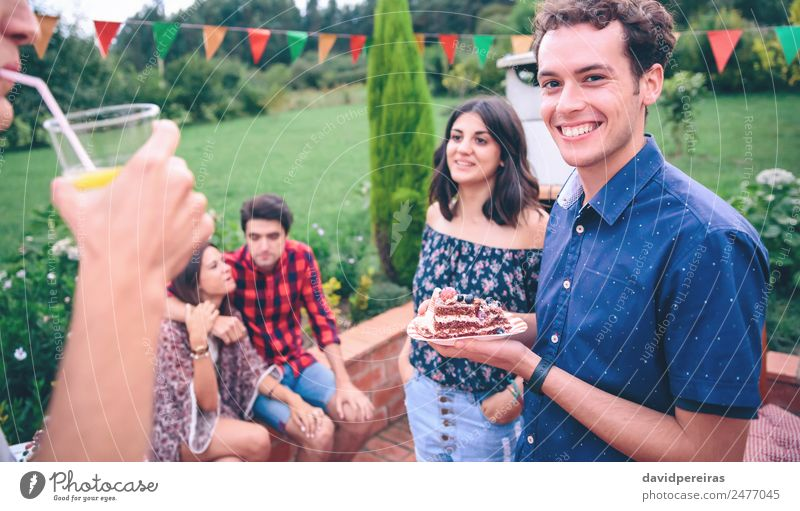 Man with piece of cake in a summer barbecue Lunch Lemonade Plate Lifestyle Joy Happy Leisure and hobbies Summer Garden To talk Woman Adults Friendship Group