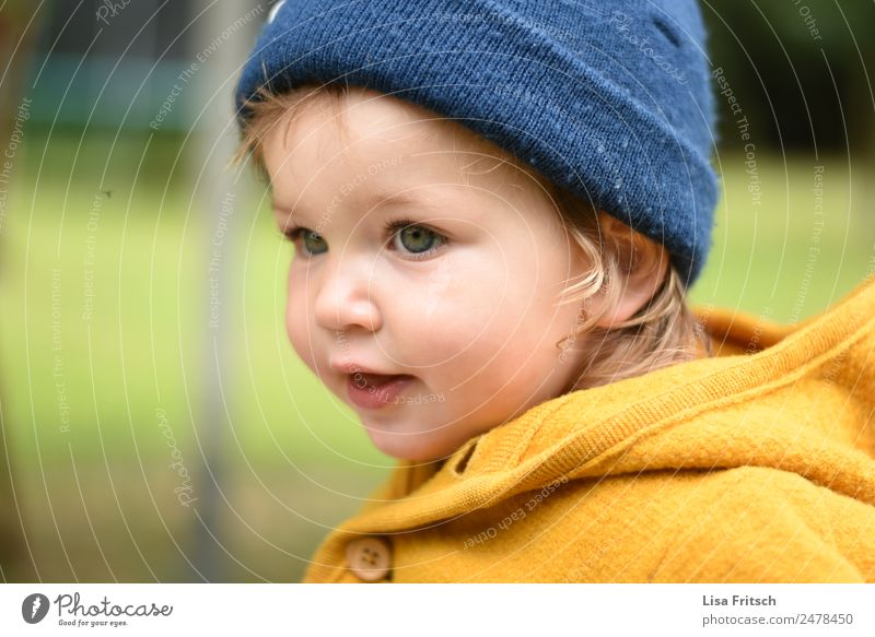 Toddler with cap Parenting Child Girl 1 Human being 1 - 3 years Cap Observe Looking Natural Blue Yellow Contentment Leisure and hobbies Infancy Concentrate