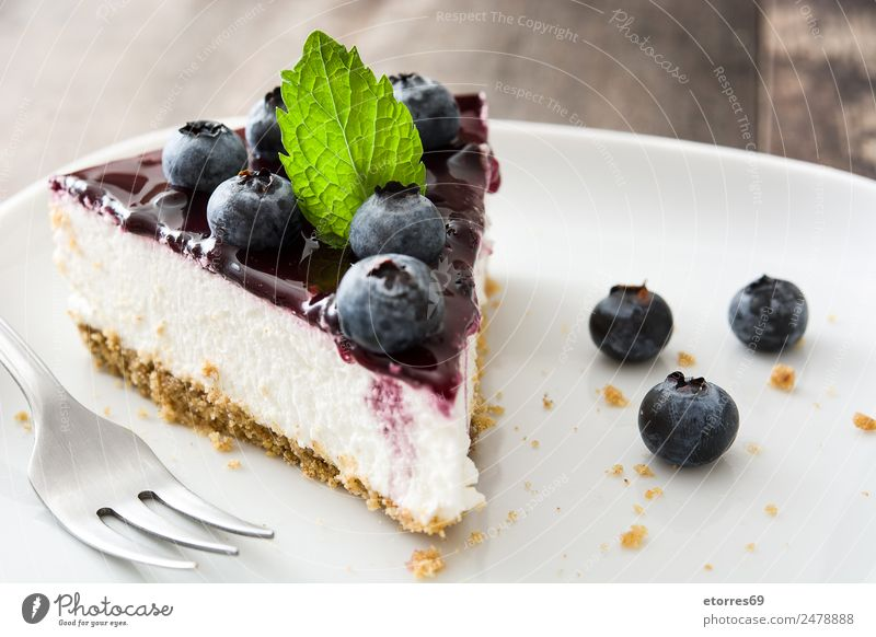 Piece of blueberry cheesecake on wooden table Cheese Cheese slice Blueberry Baked goods Cake Dessert Fruit Sweet Candy Food Healthy Eating Food photograph