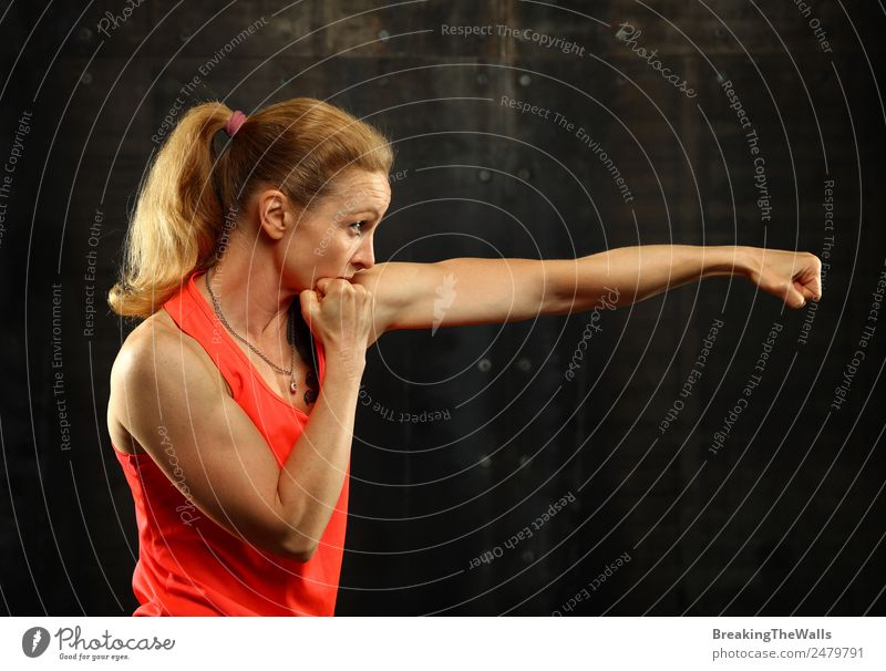 Close up side view profile portrait of one young middle age athletic woman shadow boxing in sportswear in gym over dark background, looking away Lifestyle
