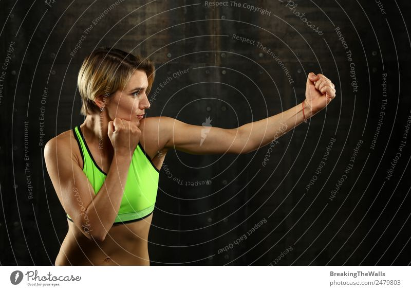 Close up side view profile portrait of one young athletic woman shadow boxing in sportswear in gym over dark background, looking away Lifestyle Sports Fitness