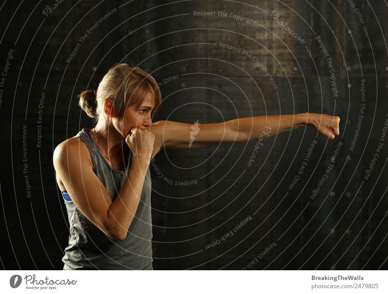 Woman shadow boxing over dark background Human being Hand Dark Black Adults Lifestyle Sports Feminine Blonde Action Arm Fitness Strong Sports Training Muscular