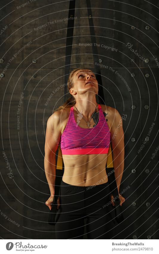 One young middle age athletic woman at crossfit training, exercising with trx suspension fitness straps over dark background, front view, looking up Sports