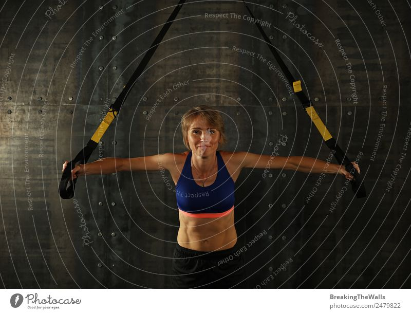 One young middle age athletic woman at crossfit training, exercising with trx suspension fitness straps over dark background, front view, looking at camera