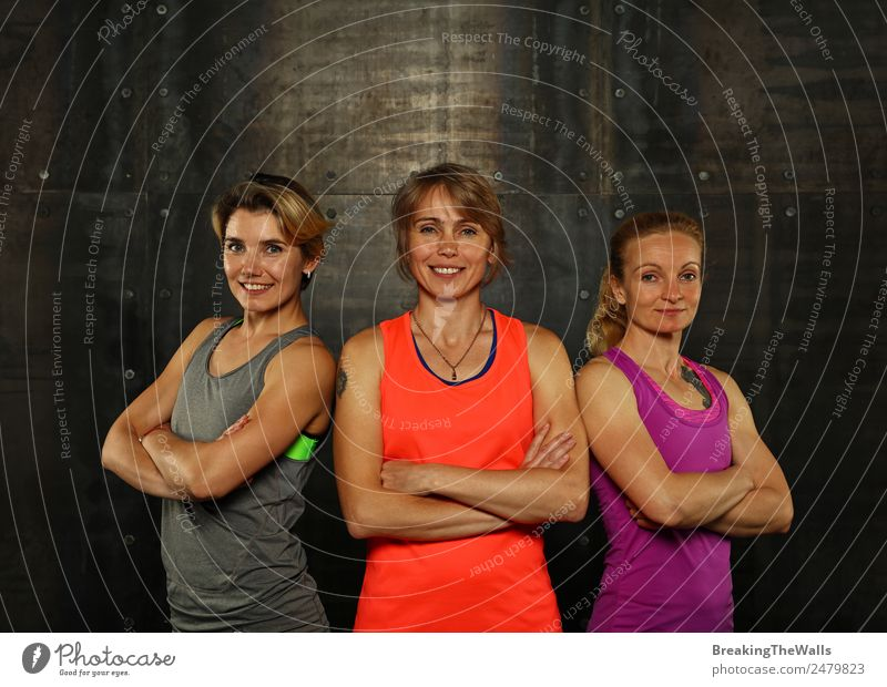 Close up front portrait of three young and middle age athletic women in sportswear in gym over dark background, looking at camera Lifestyle Athletic Fitness
