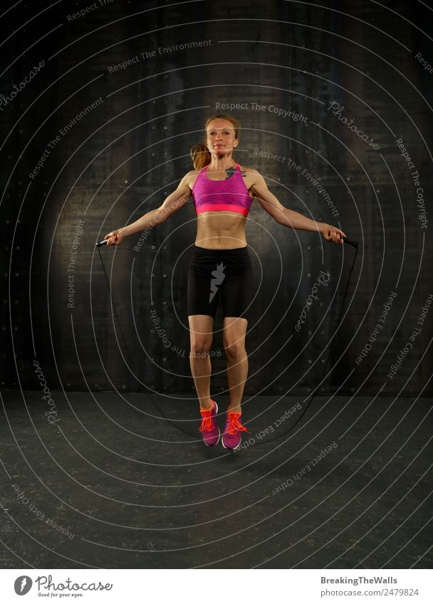 One young middle age athletic, woman training, exercising with fitness jumping rope over dark background, full length front view, looking at camera Lifestyle
