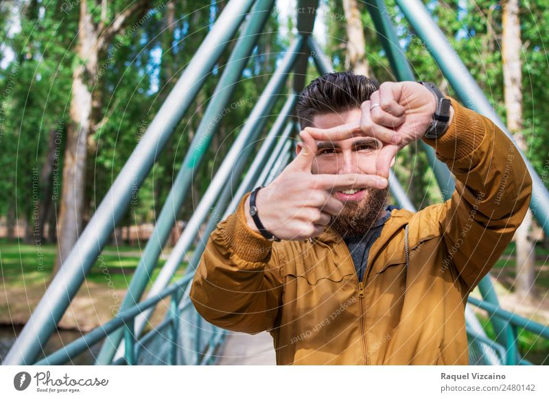 young man simulating a photographic frame with his hands Human being Nature Vacation & Travel Youth (Young adults) Green Young man Sun Hand Tree Joy Face Adults