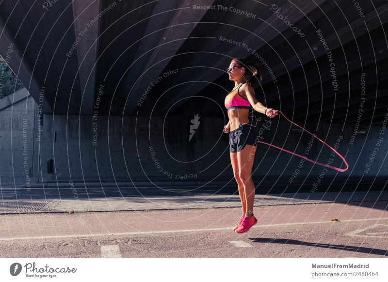 athletic woman jumping with skipping rope Woman Human being Youth (Young adults) Summer Beautiful Sun Joy 18 - 30 years Adults Lifestyle Healthy Sports Movement