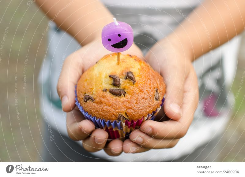 Cupcake and candle smiling in the hands of a child. Child Hand Happy Boy (child) Smiling Birthday Table Paper Candle Delicious Gastronomy Dessert Horizontal