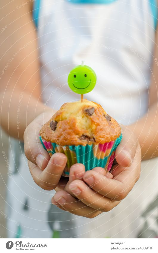 Cupcake and candle smiling in the hands of a child. Child Human being Green Hand Happy Boy (child) Food Smiling Birthday Table Paper Candle Delicious Gastronomy
