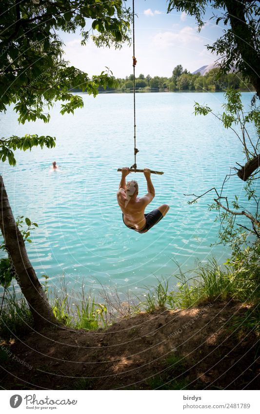 Young adults, teenagers jump from a rope into a quarry pond Leisure and hobbies Adventure Summer vacation Lake Baggersee Beach vacation Masculine