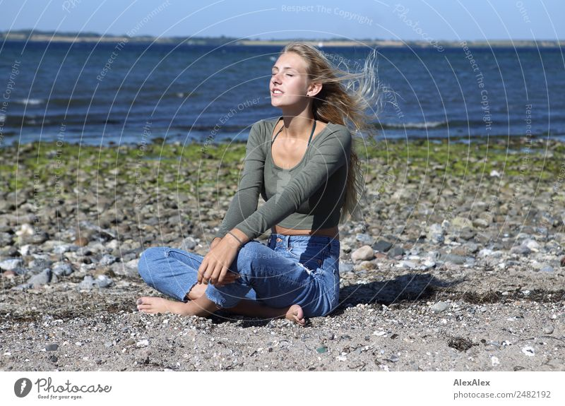 Young woman on the beach in the sun Lifestyle Happy Beautiful Well-being Summer Summer vacation Sun Sunbathing Beach Ocean Waves Youth (Young adults)