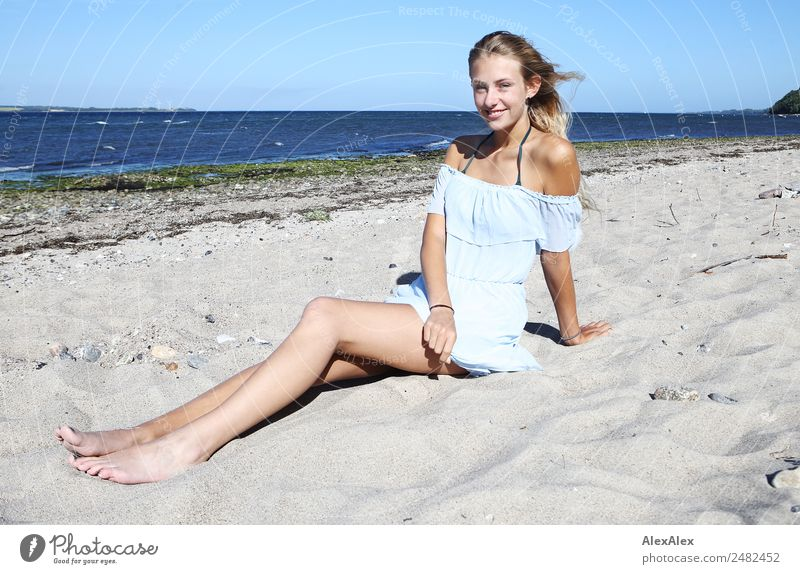 Young woman on the beach Lifestyle Joy Happy Beautiful Well-being Relaxation Summer Summer vacation Sun Sunbathing Beach Ocean Youth (Young adults) Legs