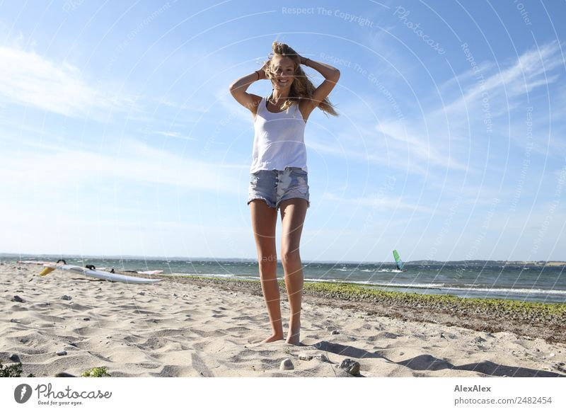 Young, slim woman on the beach of the Baltic Sea in summer wind Lifestyle pretty Relaxation Summer Summer vacation Sun Sunbathing Beach Ocean Waves Young woman