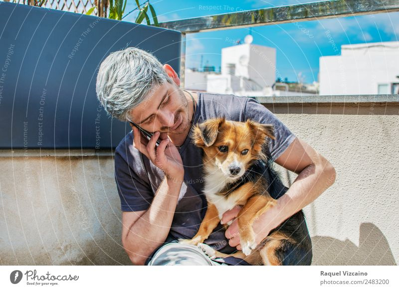 Young man talking on the phone while caressing his dog Cellphone Masculine Man Adults Face Arm 1 Human being 18 - 30 years Youth (Young adults) Garden Animal
