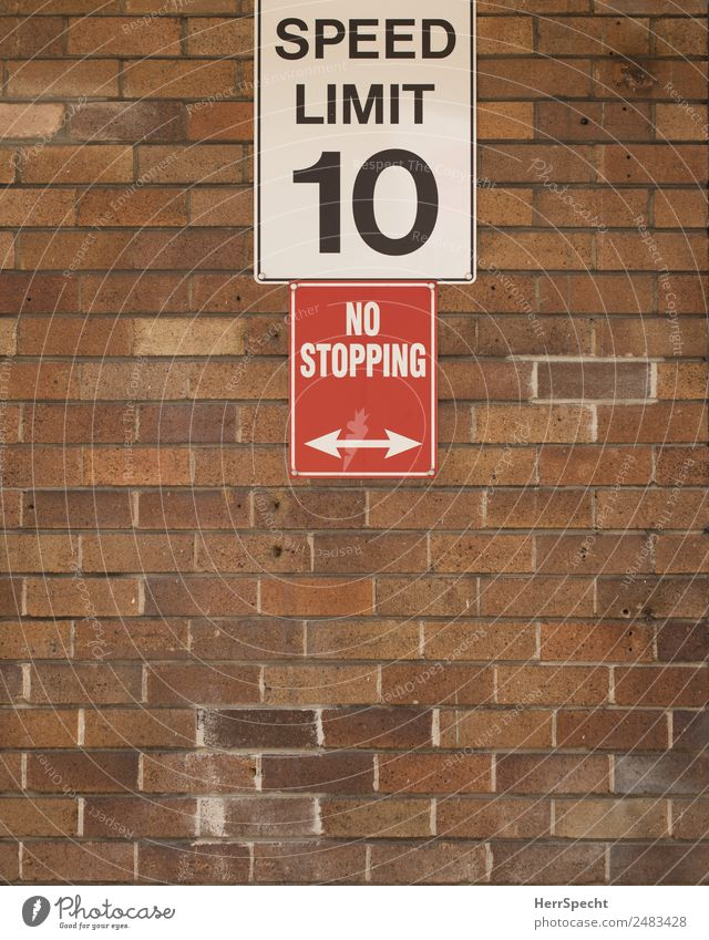 going slow Wall (barrier) Wall (building) Stone Characters Signs and labeling Signage Warning sign Town Brown Red White Speed limit No standing Brick wall