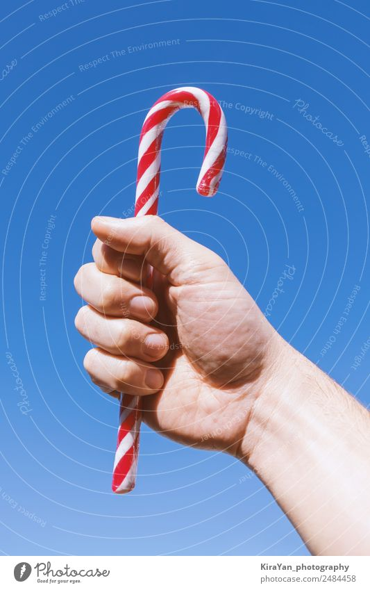 Man's hand holds traditional Christmas striped candy cane Sky Christmas & Advent Blue White Hand Red Winter Adults Feasts & Celebrations Design Modern