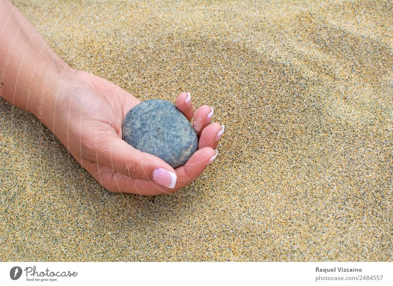 Beautiful hand holding a stone, on a beach sand background. Lifestyle Summer Summer vacation Beach Feminine Hand Sand Sun Beautiful weather Stone To enjoy
