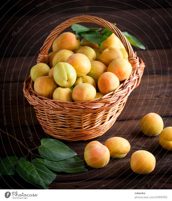 Ripe yellow apricots Fruit Nutrition Vegetarian diet Diet Table Nature Leaf Wood Fresh Natural Juicy Brown Yellow Colour Basket agriculture Apricot background