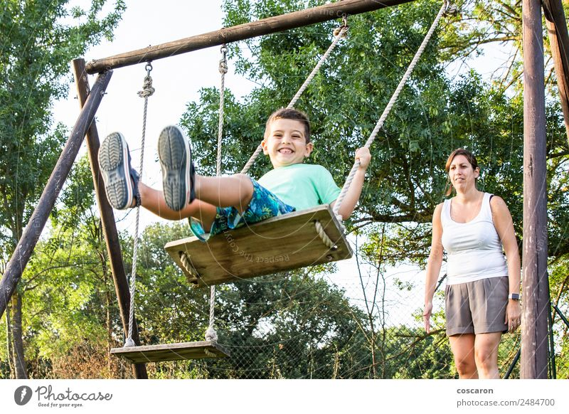Mother swinging her son on a swing Lifestyle Joy Happy Beautiful Relaxation Leisure and hobbies Playing Child Human being Boy (child) Woman Adults Man Parents