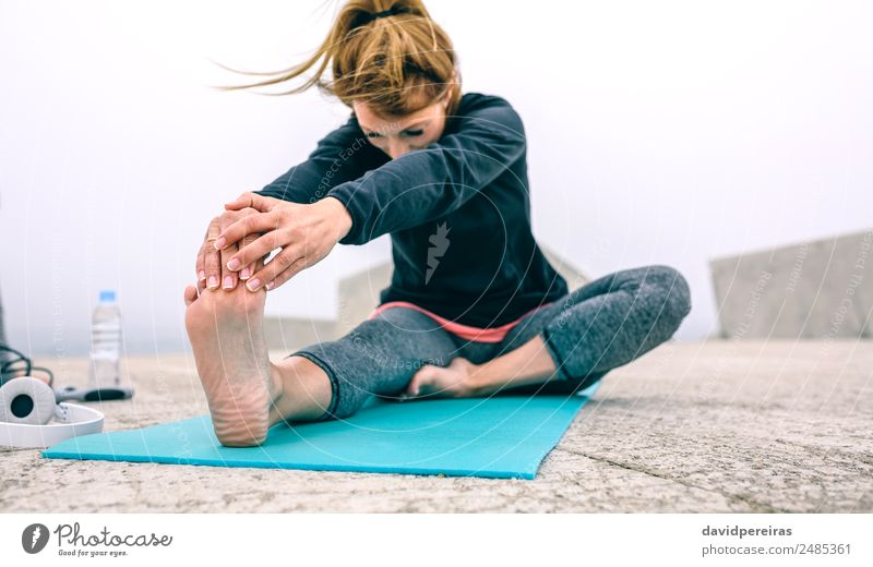Young woman stretching legs by sea pier Bottle Lifestyle Beautiful Wellness Calm Winter Sports Yoga Human being Woman Adults Hand Feet Fog Concrete Fitness