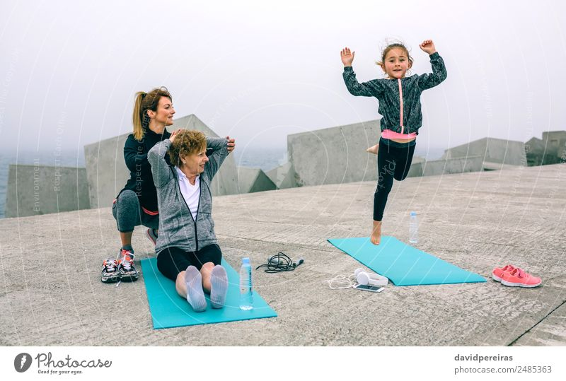 Girl jumping while women train Bottle Lifestyle Happy Wellness Sports Child Telephone Human being Woman Adults Mother Grandmother Family & Relations Fog