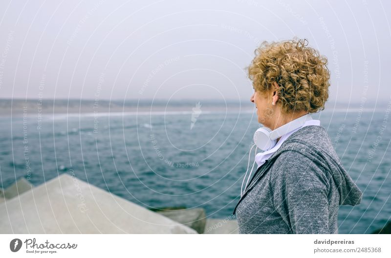 Senior sportswoman looking at the sea Lifestyle Calm Leisure and hobbies Ocean Sports Human being Woman Adults Grandmother Fog Concrete Old Athletic Authentic