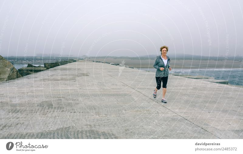 Senior sportswoman with headphones running Lifestyle Happy Wellness Ocean Sports Jogging Camera Human being Woman Adults Grandmother Fog Concrete Old Fitness